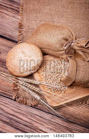 Fresh bread, harvest on the farm, ears of wheat, burlap sack of grain, a table of old wood, close-up bread, spilling wheat
