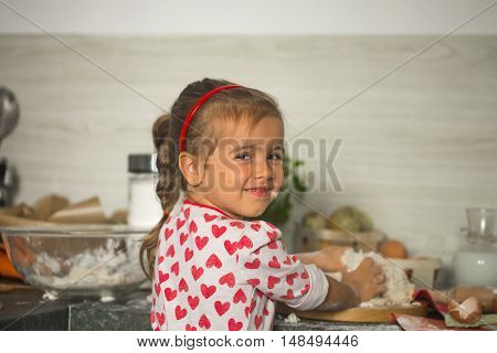 beautiful little girl Baker on kitchen with ingredients for baking