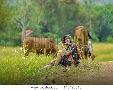 young women and cows in green pastures .