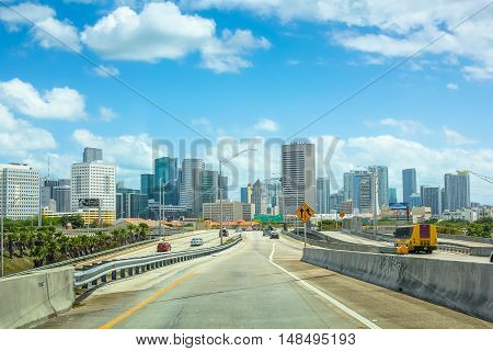 Miami, Florida, United States - April 8, 2012: cars driving on Miami Highway or Interstate 95, in the direction of South Miami. Downtown Miami skyline in the background.