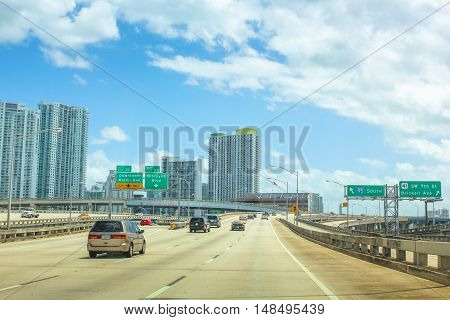 Miami, Florida, United States - April 8, 2012: car travel through Miami Highway in the direction of Downtown Miami Ave. Miami skyscrapers skyline in the background.