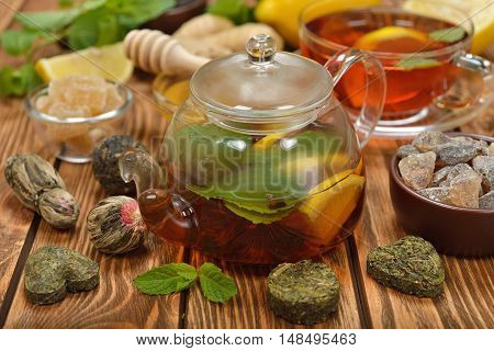Fresh tea in glass teapot on a brown background