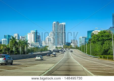 Miami, Florida, United States - April 8, 2012: cars driving on Miami Highway in the direction of Miami Downtown. Miami buildings skyline in the background.