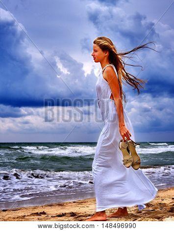 Summer girl sea. Girl walk on beach sea. Heavy clouds under sea.