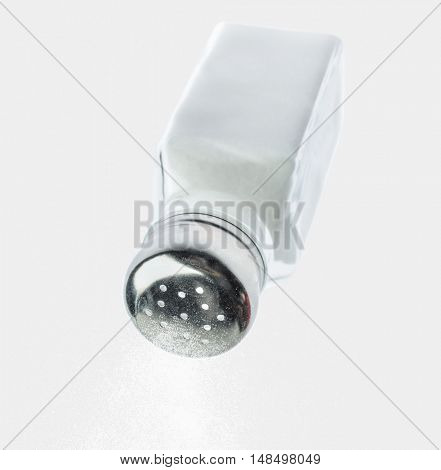 Pouring salt from a salt shaker on white background