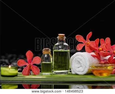 Spa setting and long leaf with red orchid ,towel,oil