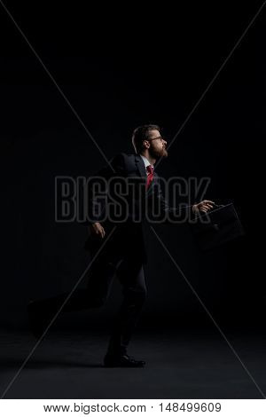 Businessman running hurry over black background. Time, business and office concept.