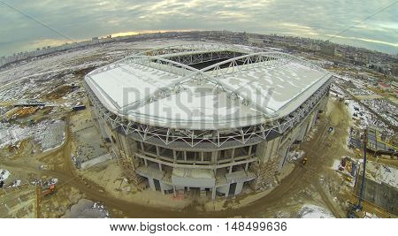 Construction of a football stadium near the city at sunset, aerial view