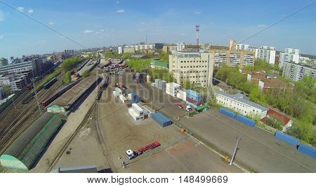 Containers at a railway station in the city on a sunny day, aerial view