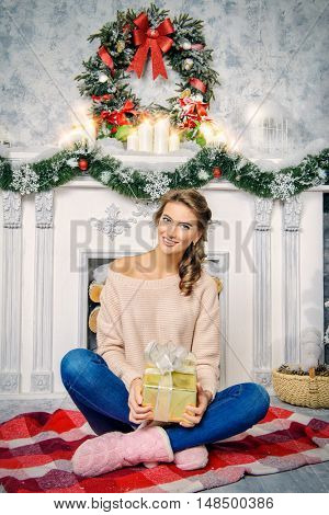 Charming young woman celebrating Christmas at home by a fireplace, beautifully decorated for Christmas.
