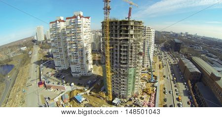 Construction of multi-storey residential building next to the road and park, aerial view