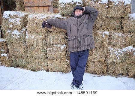 Happy elderly man leaned on bales of hay in the winter