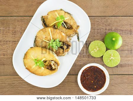 Fried fish with chili sauce on a white plate Wooden background
