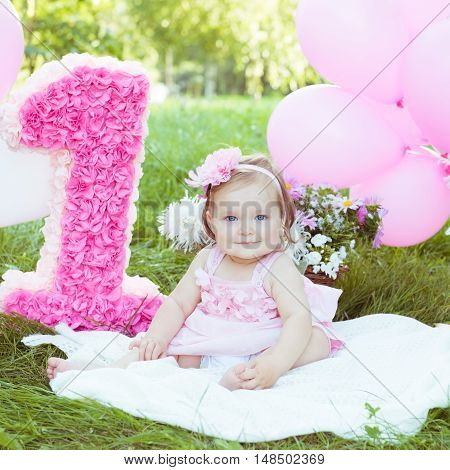 Happy little caucasian girl outside with pink balloons. 1 year