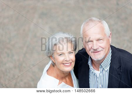 Smiling senior couple in front of a wall
