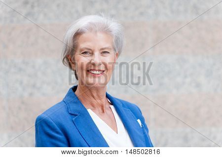 Happy senior woman in front of a wall