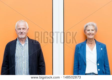 Happy senior couple in front of orange background