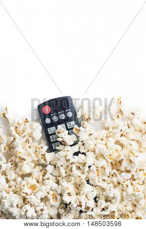 Tasty popcorn and tv remote control. Top view.