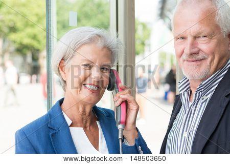 Senior couple call in a phone box