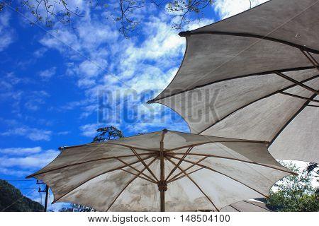 Big two white umbrellas under the blue sky