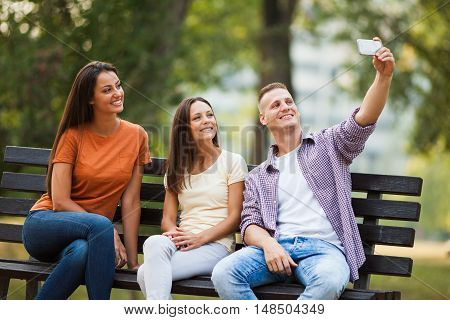 Three friends are sitting on bench in park and taking selfie with mobile phone.