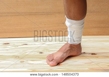 gauze bandage the foot treating patient ulcers male is wrap his injury on wooden floor background