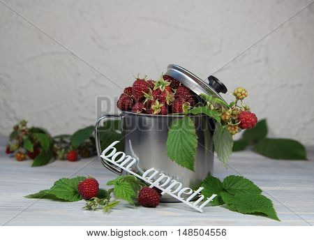 raspberry in a metal mug with a cover and an inscription bon appetite