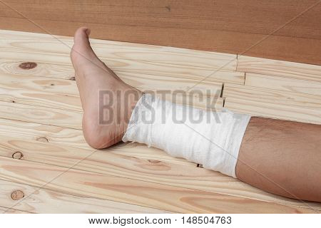 Gauze bandage of physician the treating case with ankle Injured on wooden floor background