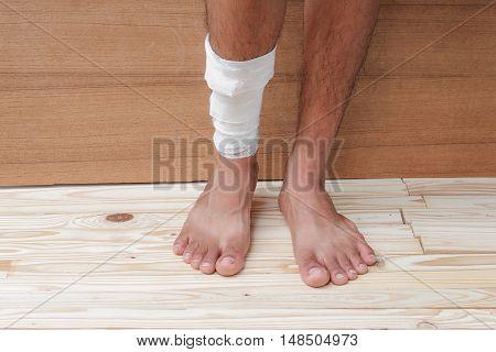 Gauze bandage the treating case with ankle Injured on wooden floor background