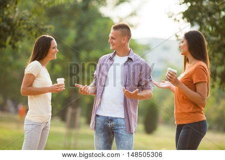 Three friends are standing in park and talking.