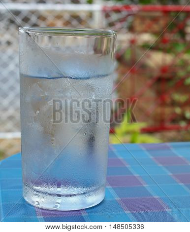 Cold Water on Wood Table. glass of Cool fresh drink with ice cube. :Select focus with shallow depth of field.