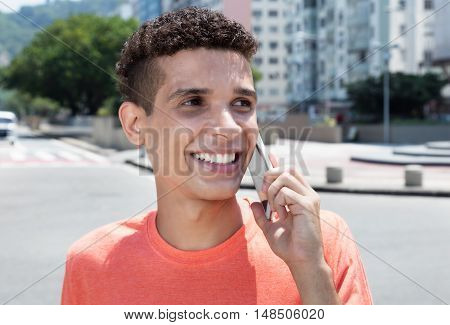 Latin man in shirt talking at phone in the city