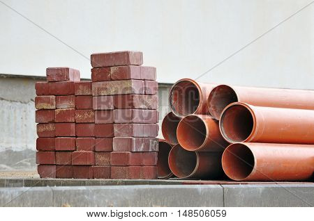 The process of laying engineering communications. Warehouse of red sidewalk square tiles and sewer pipes.