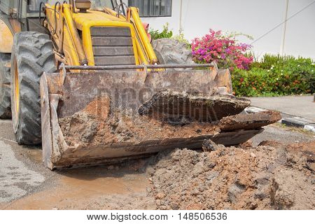 Excavator selective focus bulldozer work a hole the repair of pipe water and sewerage on road
