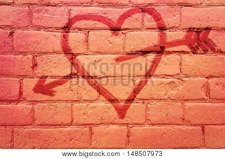 on a brick wall painted heart pierced by an arrow. background