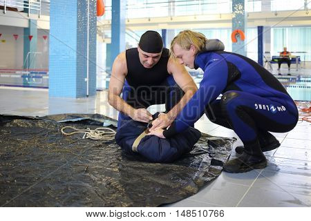 RUSSIA, MOSCOW - DEC 10, 2014: Two man is packing outfit on the black mat in Training center for civil defense and emergency situations of Moscow.