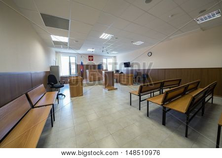 MOSCOW, RUSSIA - JUL 1, 2015:  wooden furniture in court of law hall with flag, screen and clock.