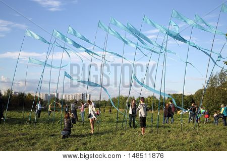 RUSSIA, MOSCOW - AUG 30, 2015: Many people is standing near many blue flags in city park.