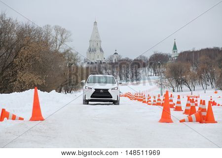 MOSCOW - FEB 14, 2015: White stylish car going on winter road on a test drive in Kolomenskoye