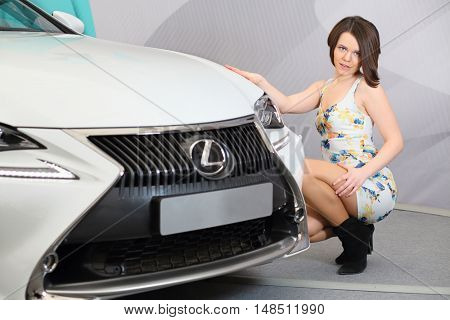 MOSCOW - FEB 14, 2015: Beautiful woman (with model release) squatted down near white car in the salon on Russian sixth test drive Lexus Master Class