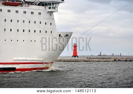 SOPOT, POLAND - JULY 15, 2013: Detail of a white passenger ship in the background of the sea the lighthouse and stormy sky. Baltic Sea, Poland.