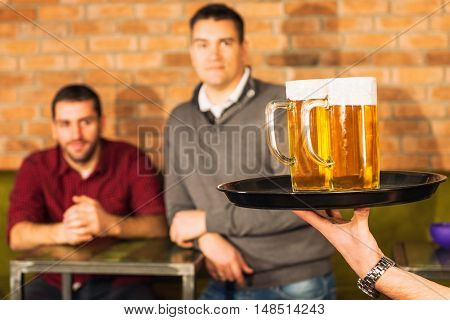 Friends in pub beer coming, toned image,