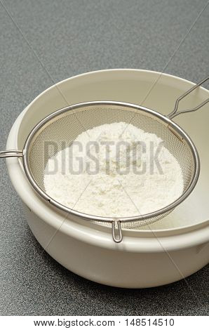 Sifting flour into a white plastic bowl