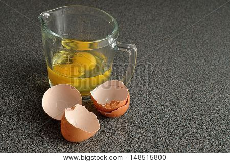Two raw eggs in a measuring cup on a Grey worktop with egg shells