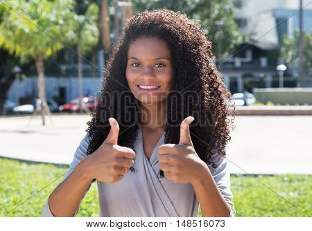 Latin woman with long curly hair showing both thumbs up outdoor in the city in the summer