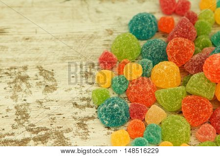 Colorful jelly beans of different sizes close to wallpaper