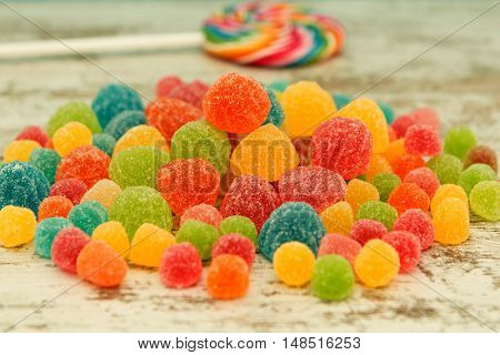 Colorful jelly beans and lollypop close to wallpaper