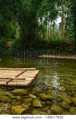 Bamboo raft floating on a calm mountain river with crystal clear water and stones on the bottom.