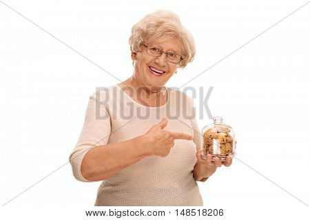 Cheerful elderly woman holding a jar full of cookies and pointing isolated on white background