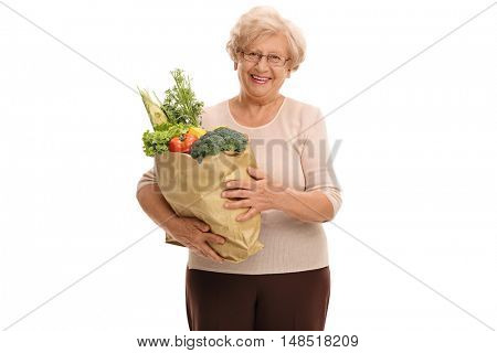 Happy mature woman holding a paper bag full of groceries isolated on white background